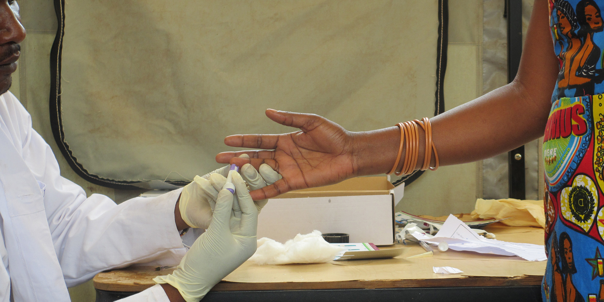 A health worker pricking a patient's finger