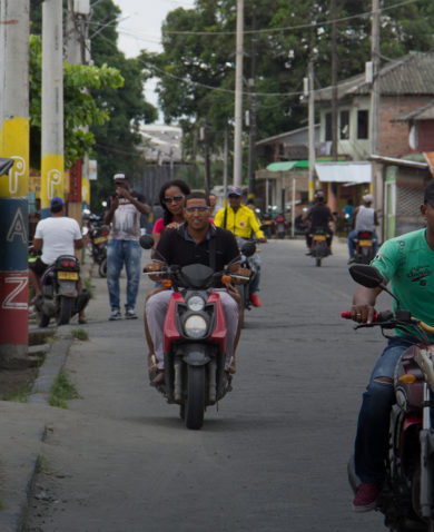 people on motorcycles in Colombia with the word paz or peace in spanish written on posts