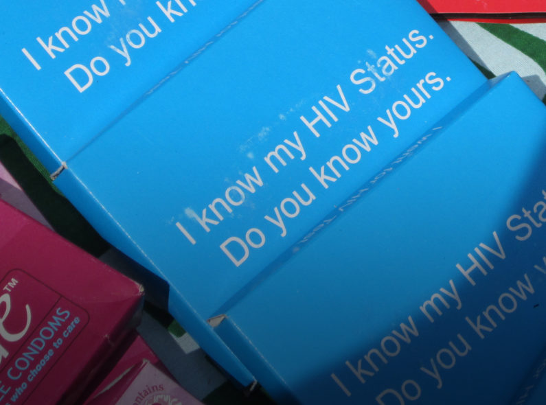 "Small boxes displayed on a table, on which are written, ""I know my HIV status. Do you know yours?"""