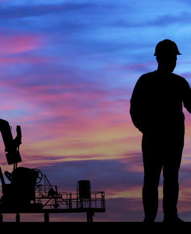 Two people shake hands in front of equipment at an oil field.