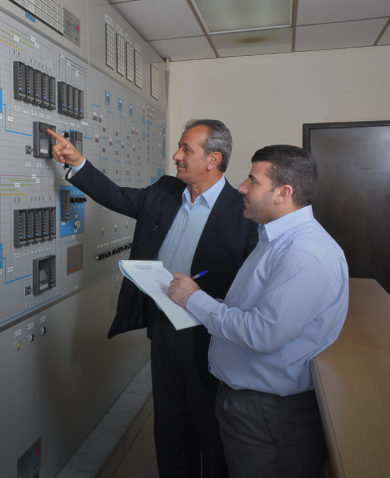 Two men examine a control panel in Jordan.