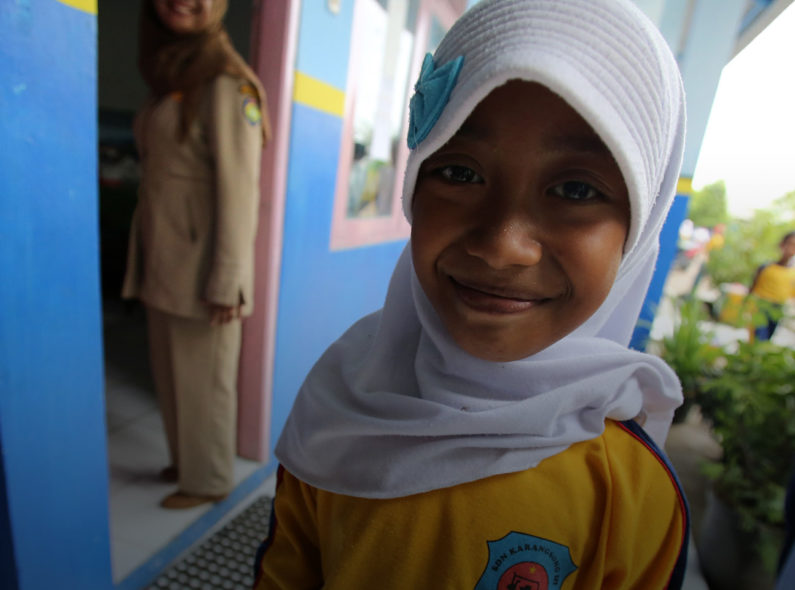 A girl smiles up at the camera