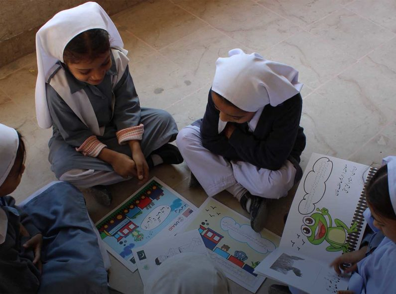 A group of four girls in Pakistan reading children's books in a school