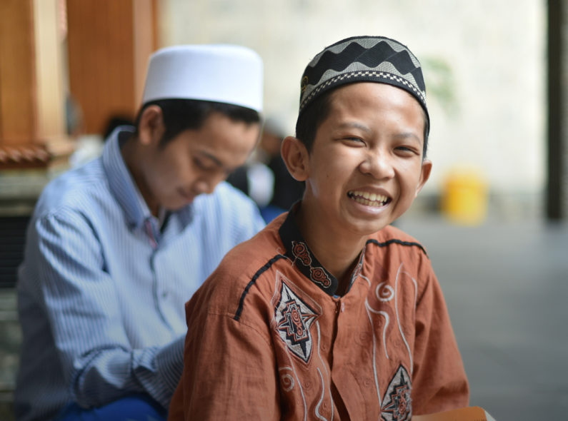 Indonesian child smiling with a book in his lap