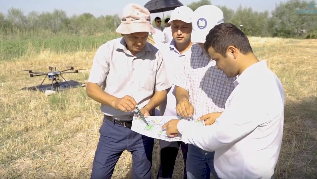 Group of men study a land survey map with drone in the background