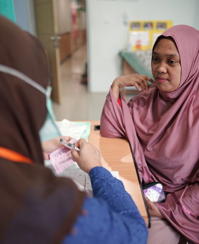 Woman talking to a community health worker in Indonesia
