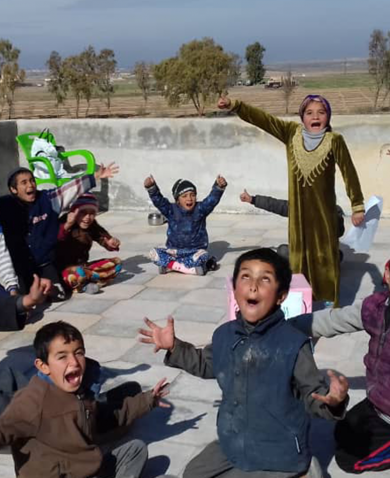 Syrian children sitting in a circle shout happily