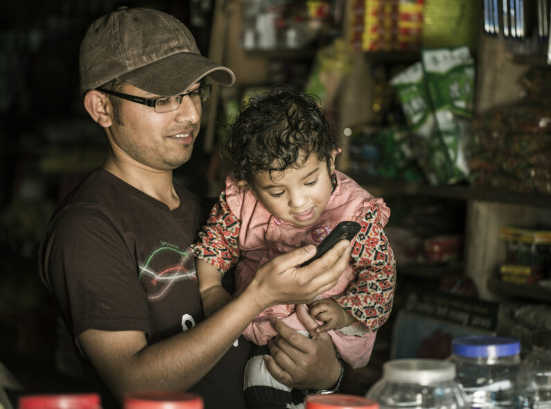 Feature image: Man holds child and both look at his smartphone