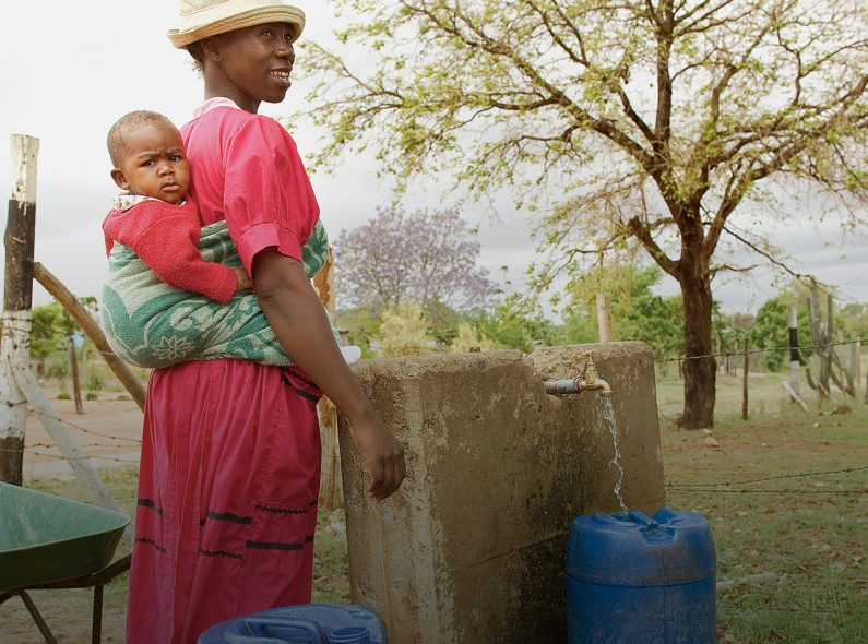 A woman and her child fill barrels with water in South Africa.