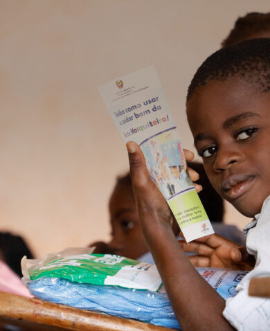 Student in Mozambique holds bed net and pamphlet about malaria.